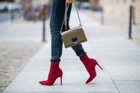 Woman's legs in jeans and red ankle boots