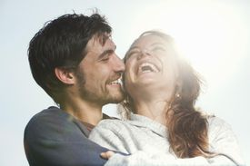 Young couple laughing together, hugging outdoors