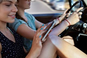 Woman scrolling on phone, while friend is driving