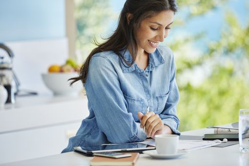 Smiling woman working reviewing paperwork at kitchen counter