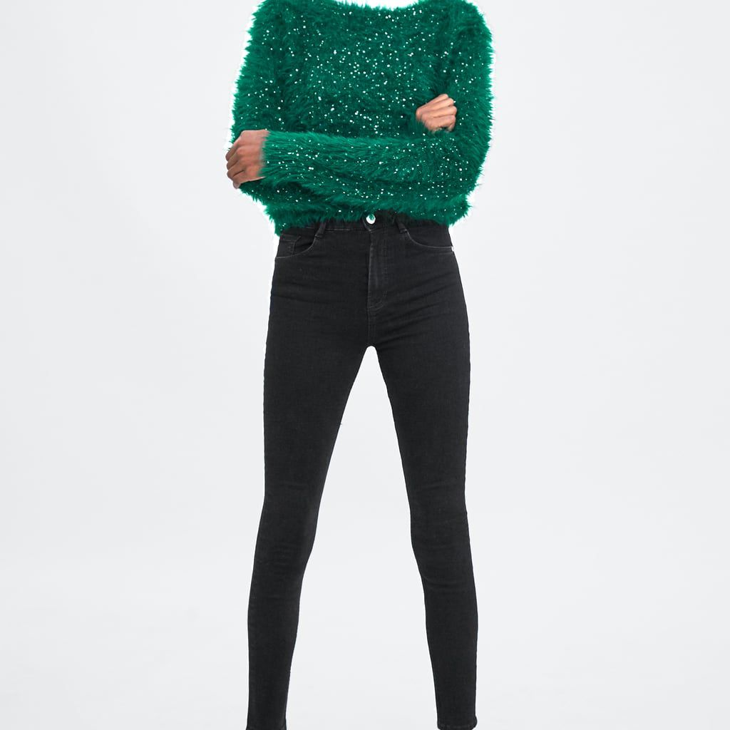 Woman in green sweater and black skinny jeans