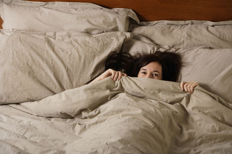 a woman is hiding under the covers looking embarrassed