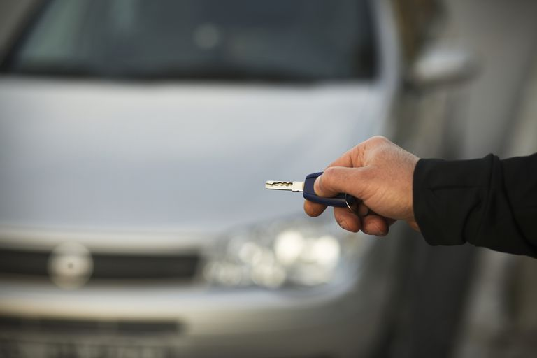 man holding keyless remote to vehicle