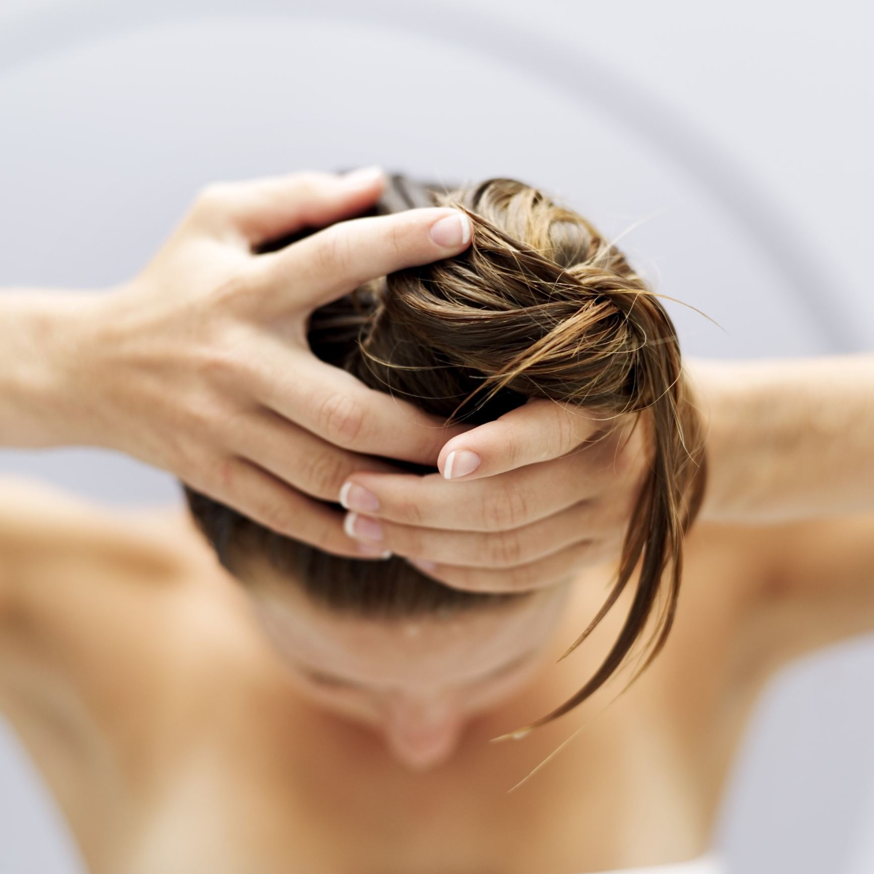 High angle view of a woman piling her hair up into a bun