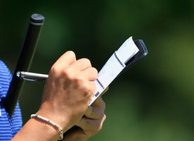 A marker in golf writes down the scores