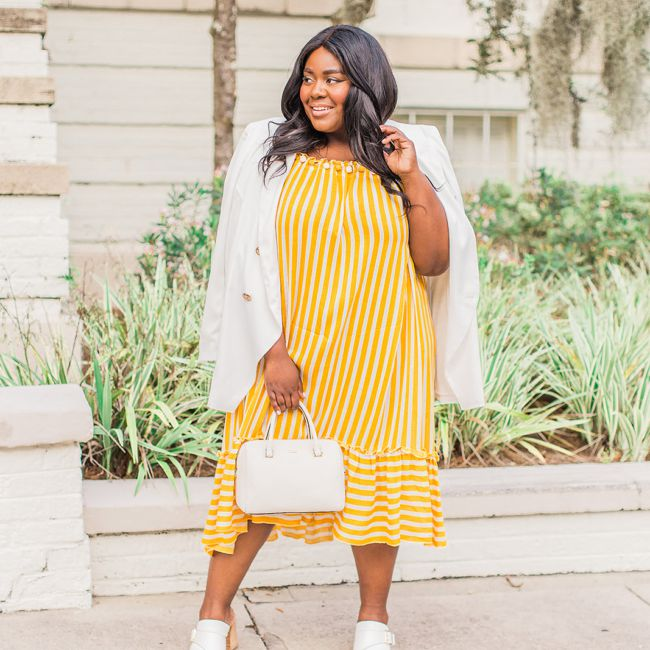 Plus size woman in yellow sundress and white blazer