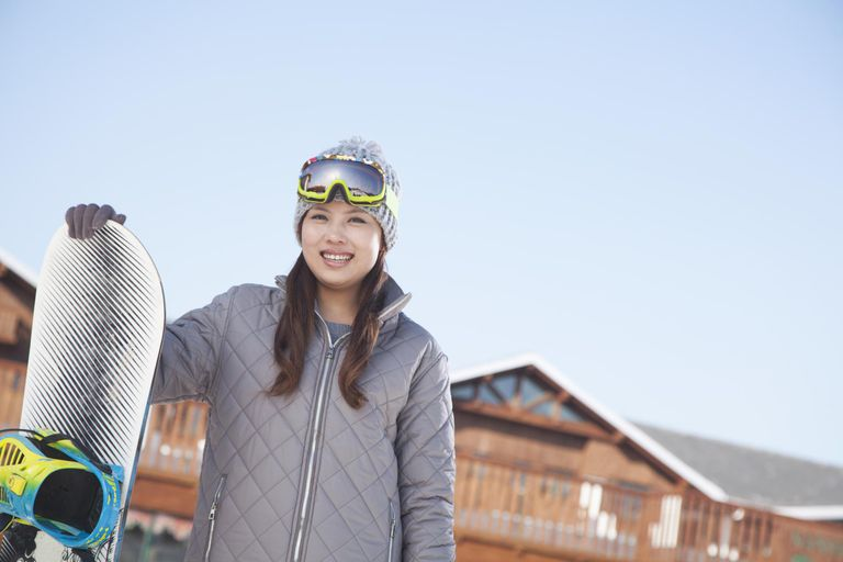 Smiling Chinese snowboarder holding snowboard