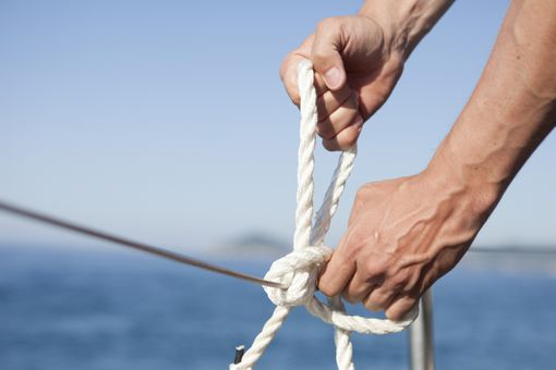 hands tying rope on a boat