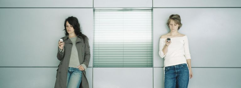 Two young women leaning against wall, looking at cell phones