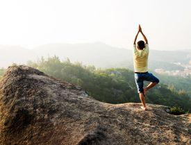 Asian man doing yoga on mountain peak