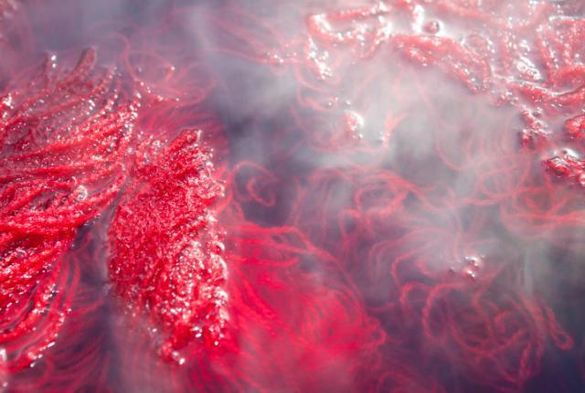 Red yarn soaking in dyeing vat