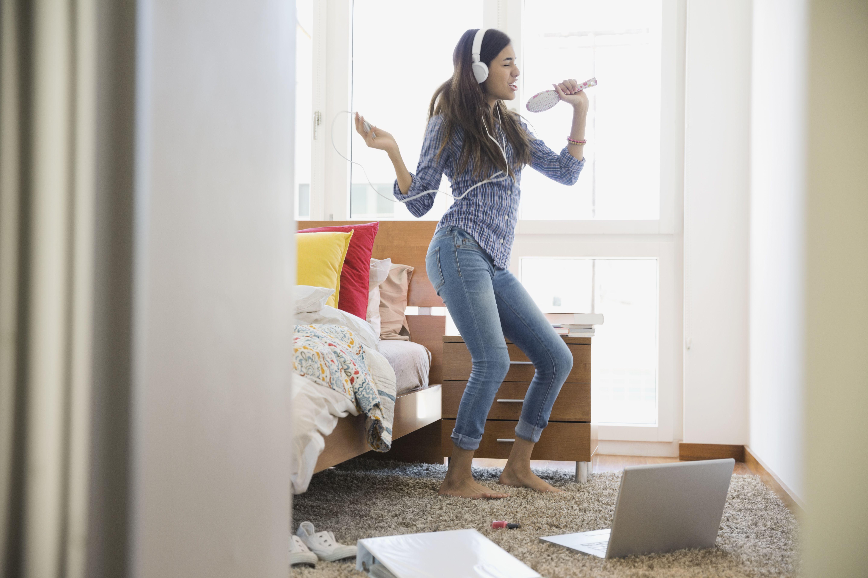 Girl with headphones on dancing to music