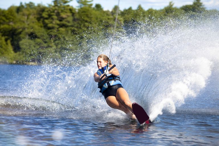 A woman waterskiing on a slalom board