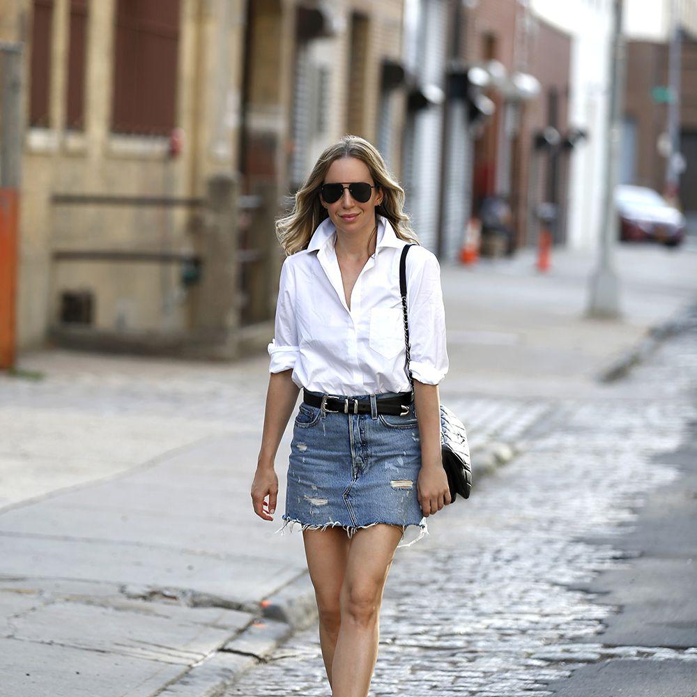 Woman wearing denim skirt and white button down shirt