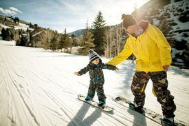 Father holding his son during snowboard lesson.