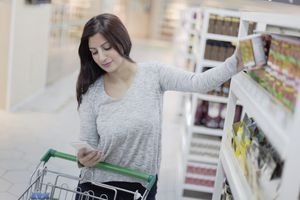 Woman Using Smart Phone to Research Product in Supermarket