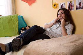 A teen girl sits on her bed.