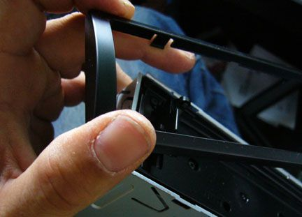 Hand holding a stereo trim plate next to its snap-in location