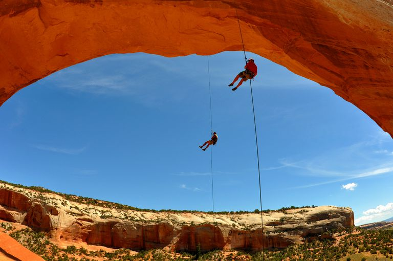 Climbers rappel off Wilson Arch near Moab, Utah.