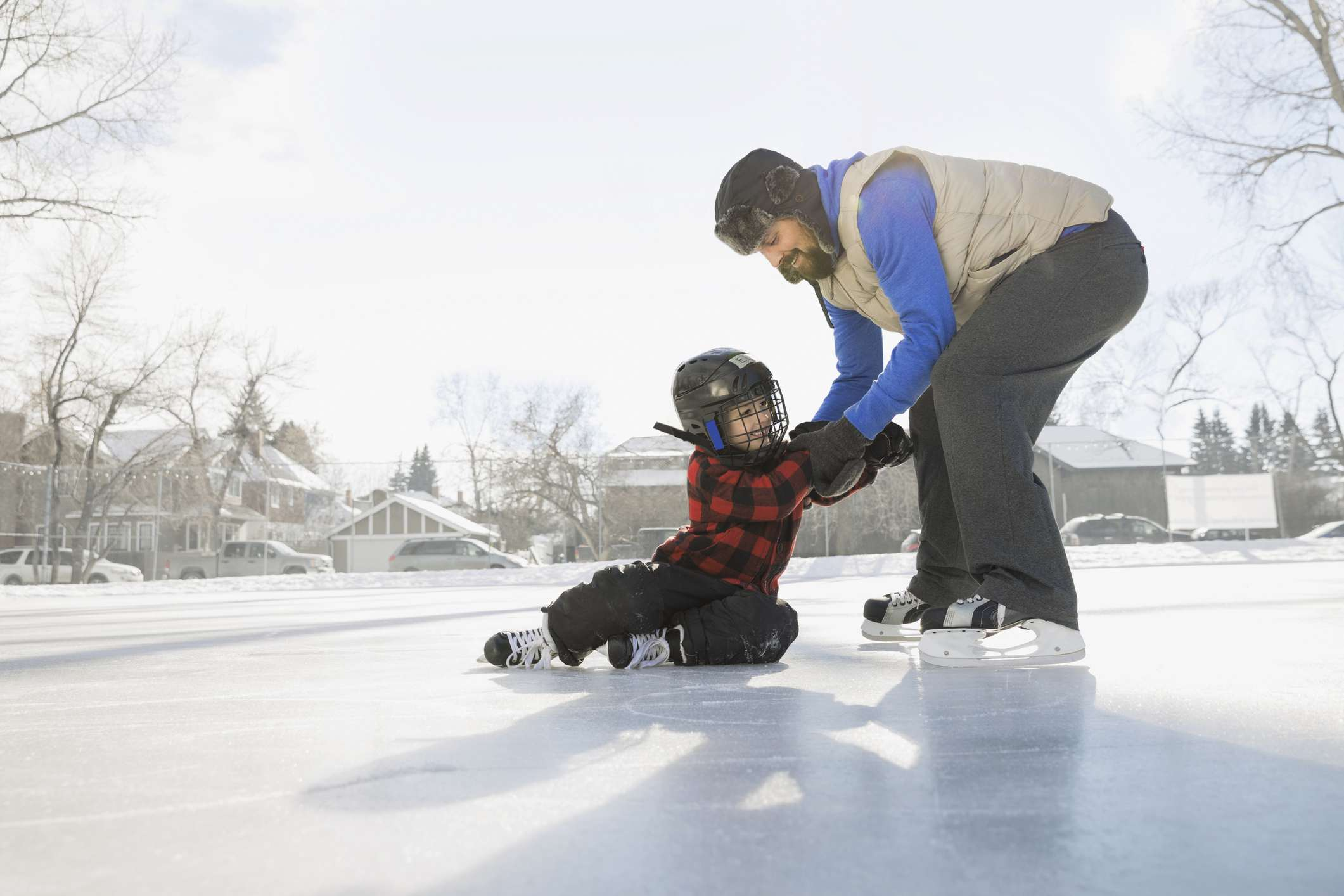 Father teaching son to ice-skate on outdoor rink