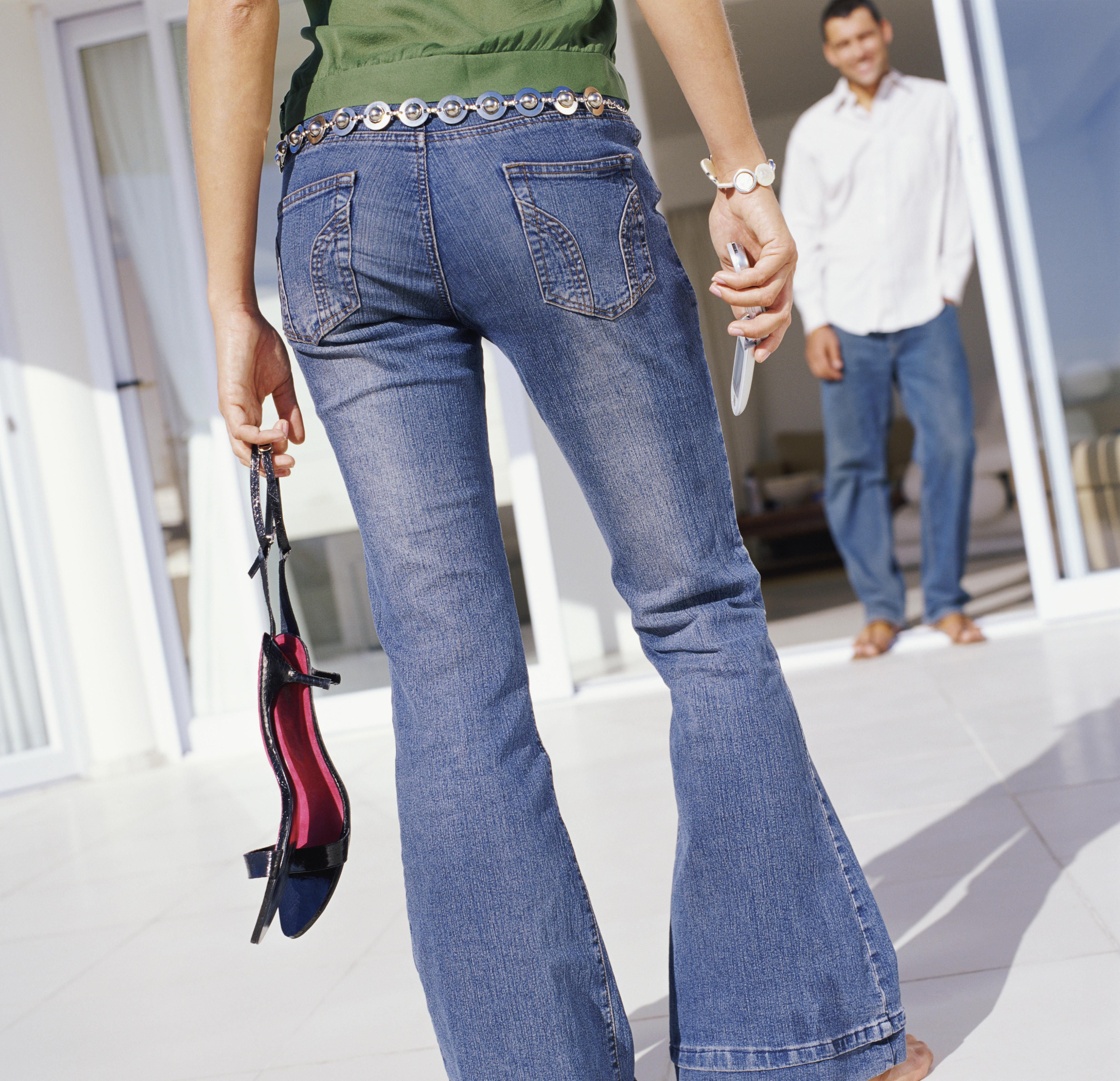 Rear View Low Section Shot of a Woman Wearing Flared Jeans and Holding a Mobile Phone