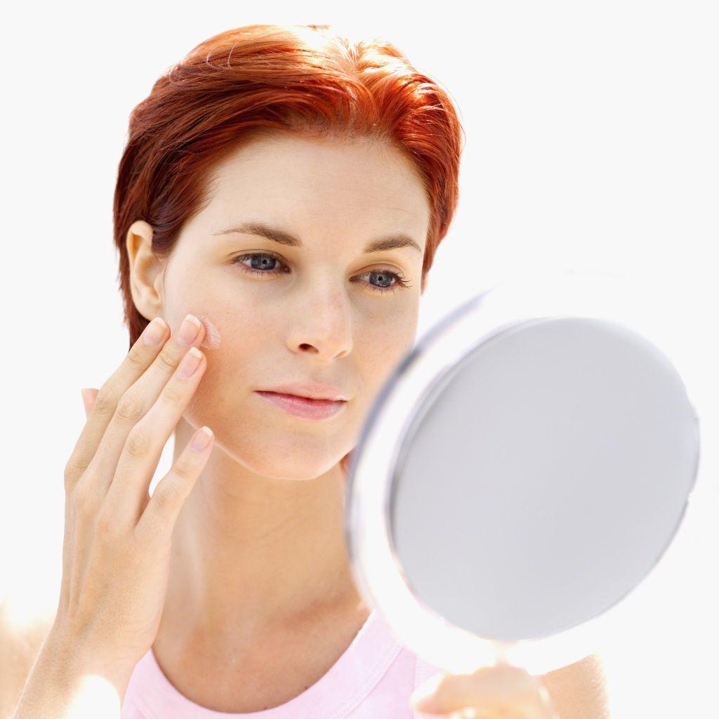 Woman looking in mirror at skin