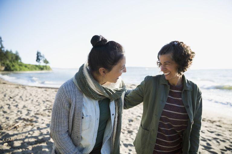 Happy women friends walking and talking on sunny beach