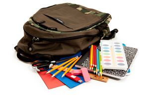 Close-Up Of Backpack And Colored Pencils On White Background