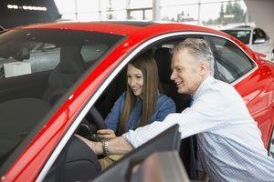 Salesman and woman looking inside car in showroom
