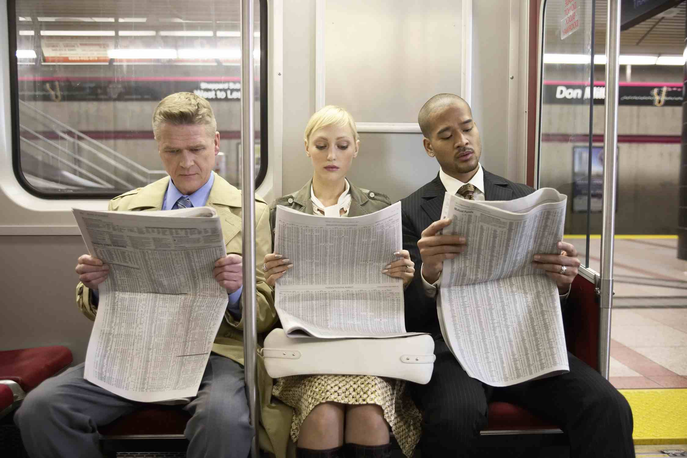 Three people reading the newspaper on a train