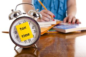 Time: Alarm clock tax time note on front. Woman background