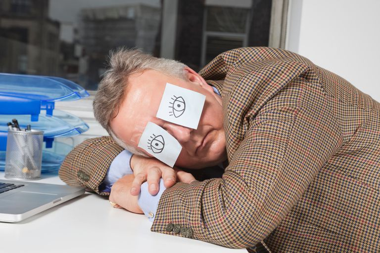 Man sleeping at desk with post-it notes drawn as eyes