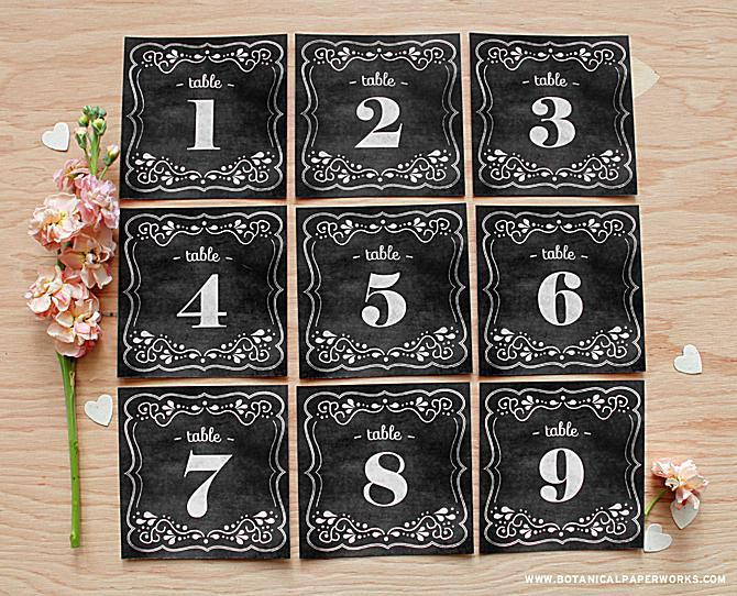A set of 1-9 chalkboard wedding table numbers on a table.