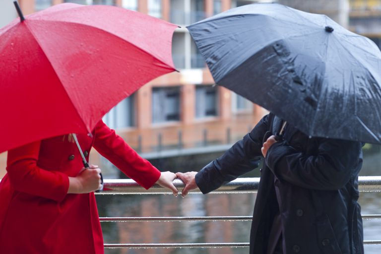 A man and a woman holding hands, hiding their faces with umbrellas.