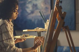 Young woman in profile painting at an easel.