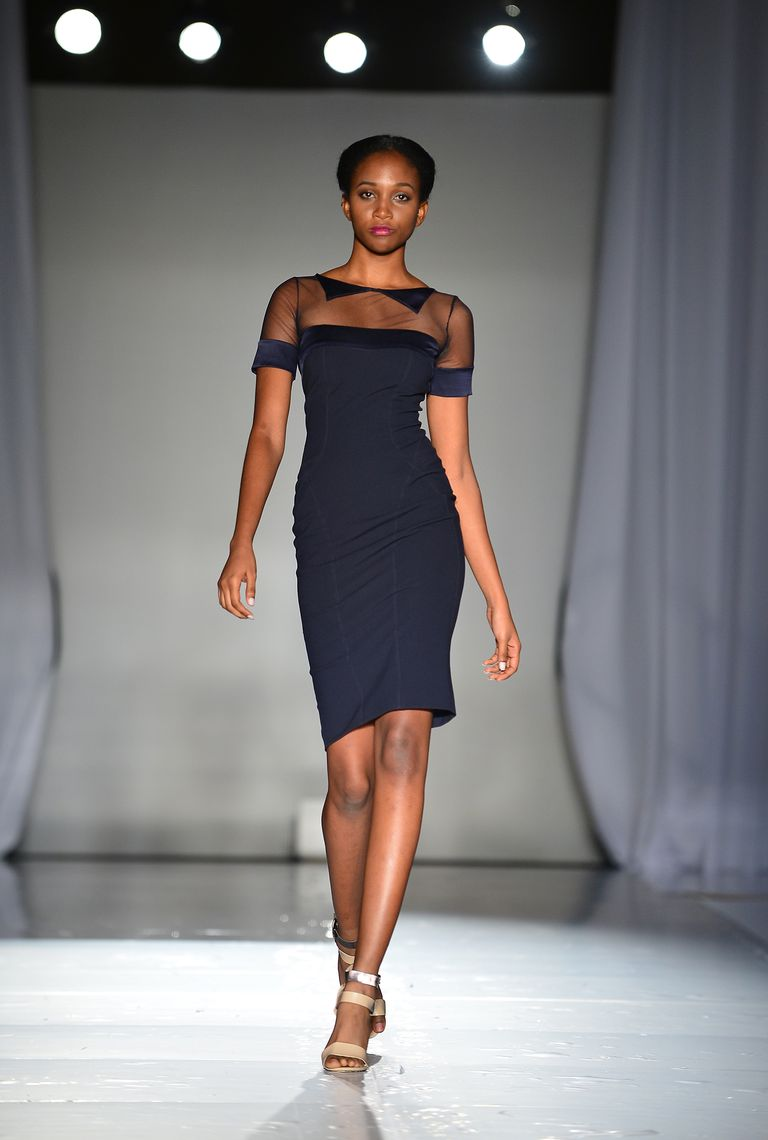 Model Walking Down Runway In Navy Dress And Neutral Sandals