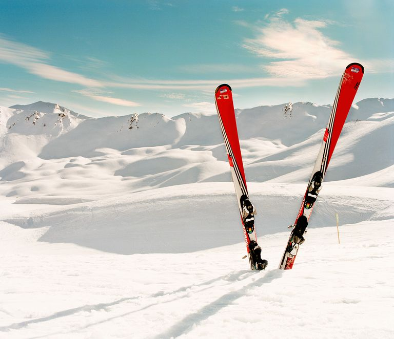 Red pair of ski standing in snow. Mountains in background.