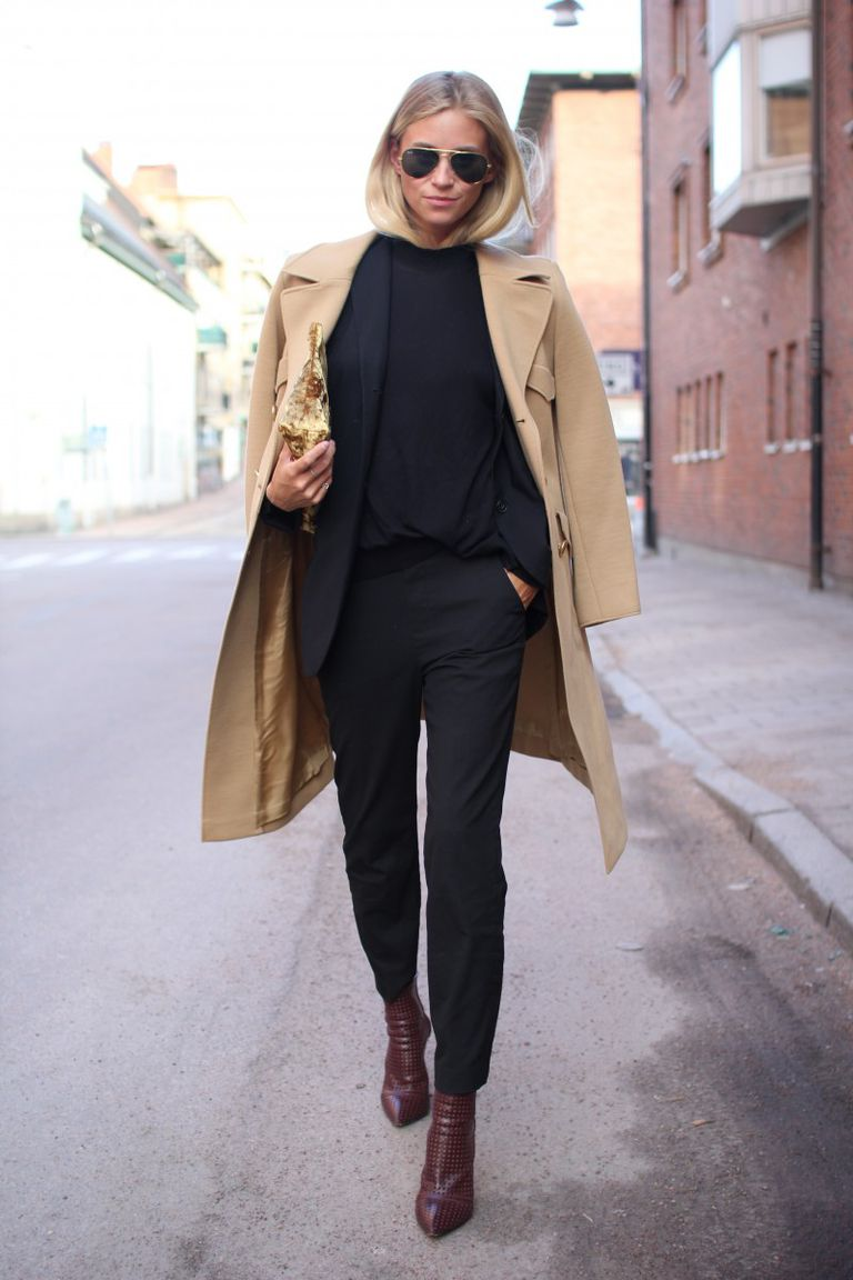 Woman in black outfit and wool camel coat