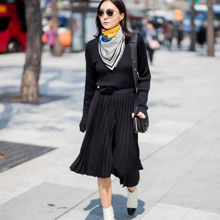 Woman wearing black top and black pleated maxi skirt with colorful silk scarf