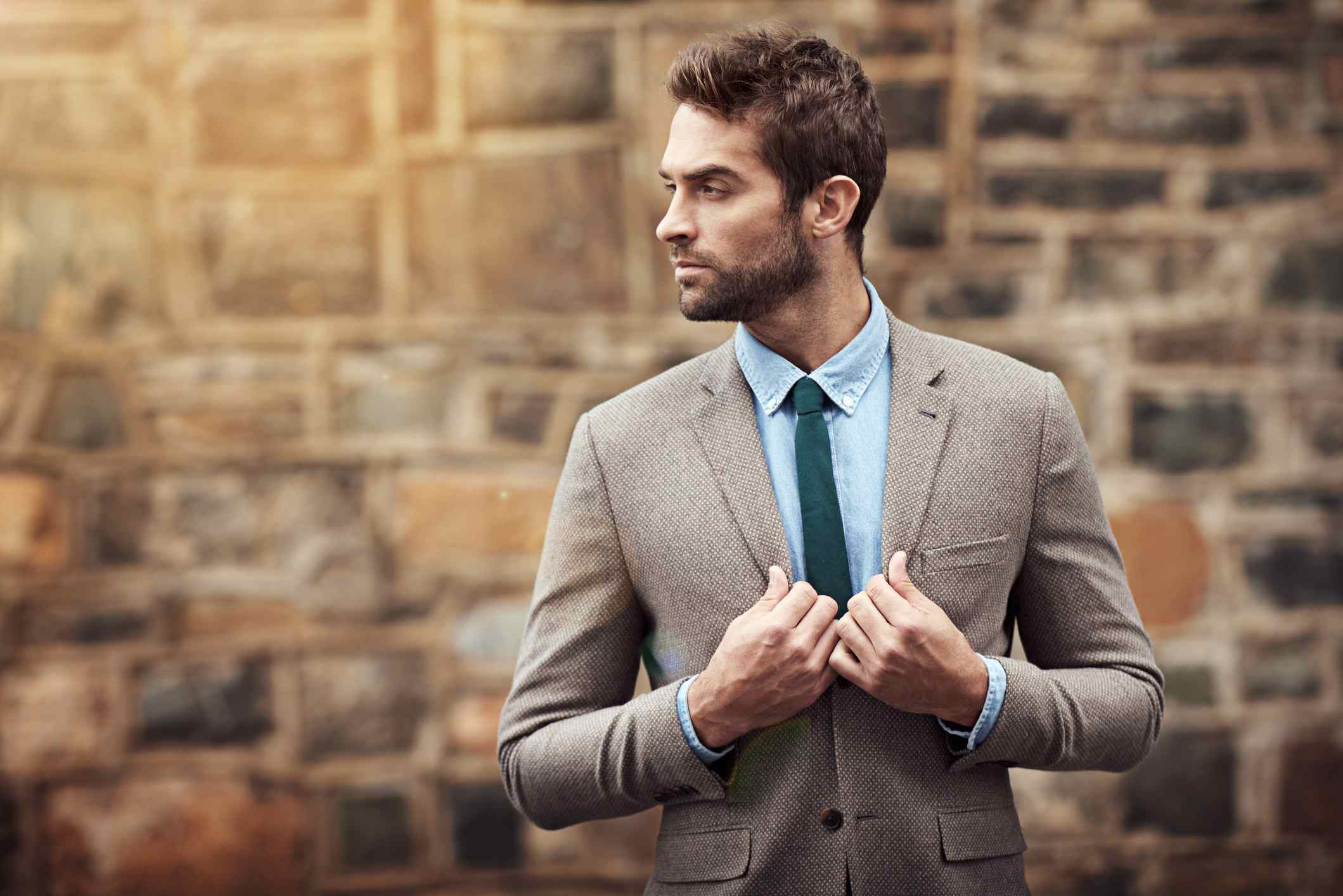 Male model posing in front of stone wall