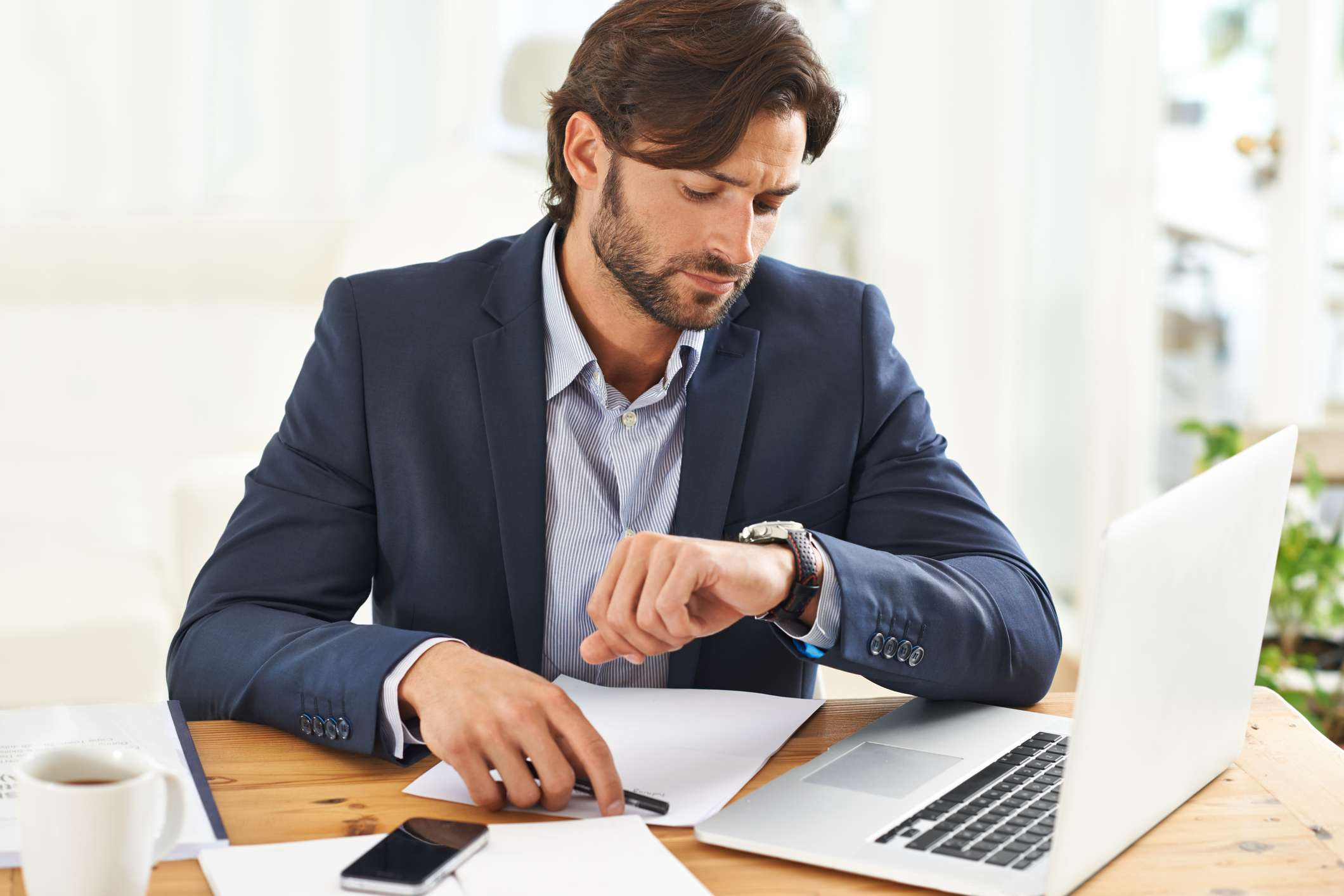 Man working on computer checking his watch