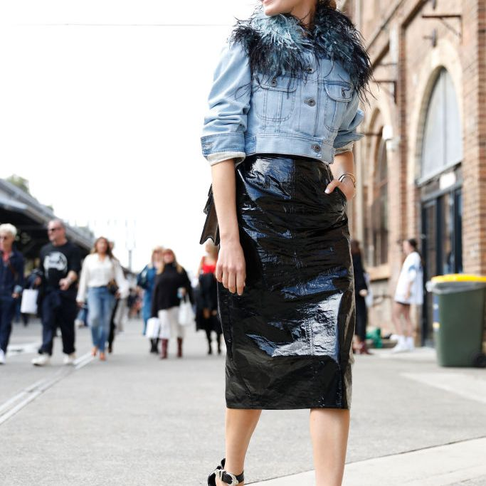 Woman wearing denim jacket and pleather skirt