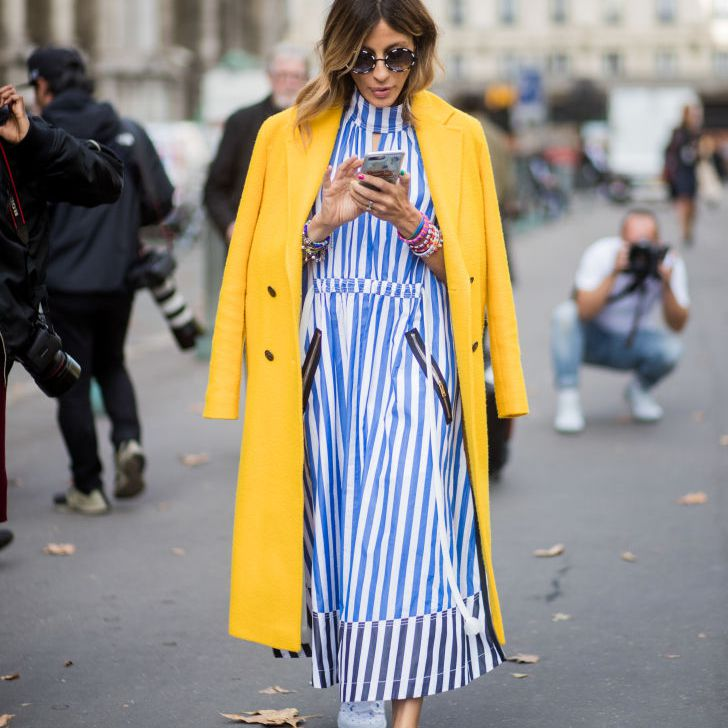 Street style woman in striped dress yellow coat and sneakers