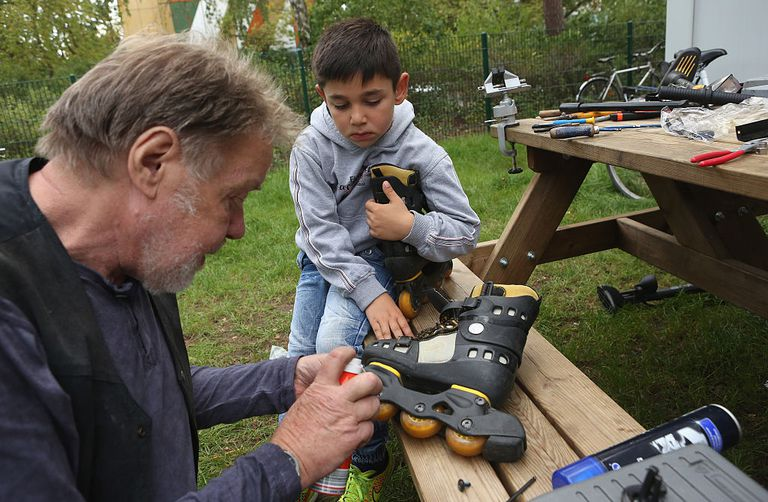 Man and child repairing rollerblades.