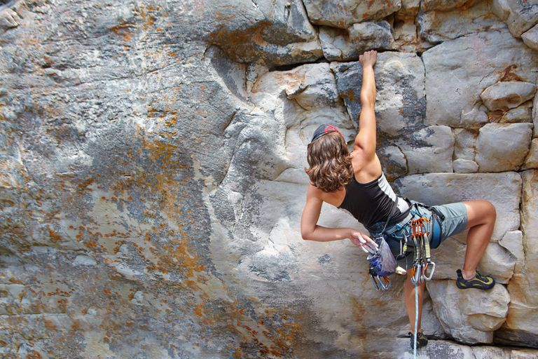 female rock climber scaling a rock face