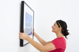 Woman hanging painting