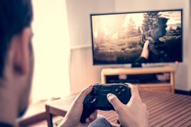 Man playing PS4 game on big TV