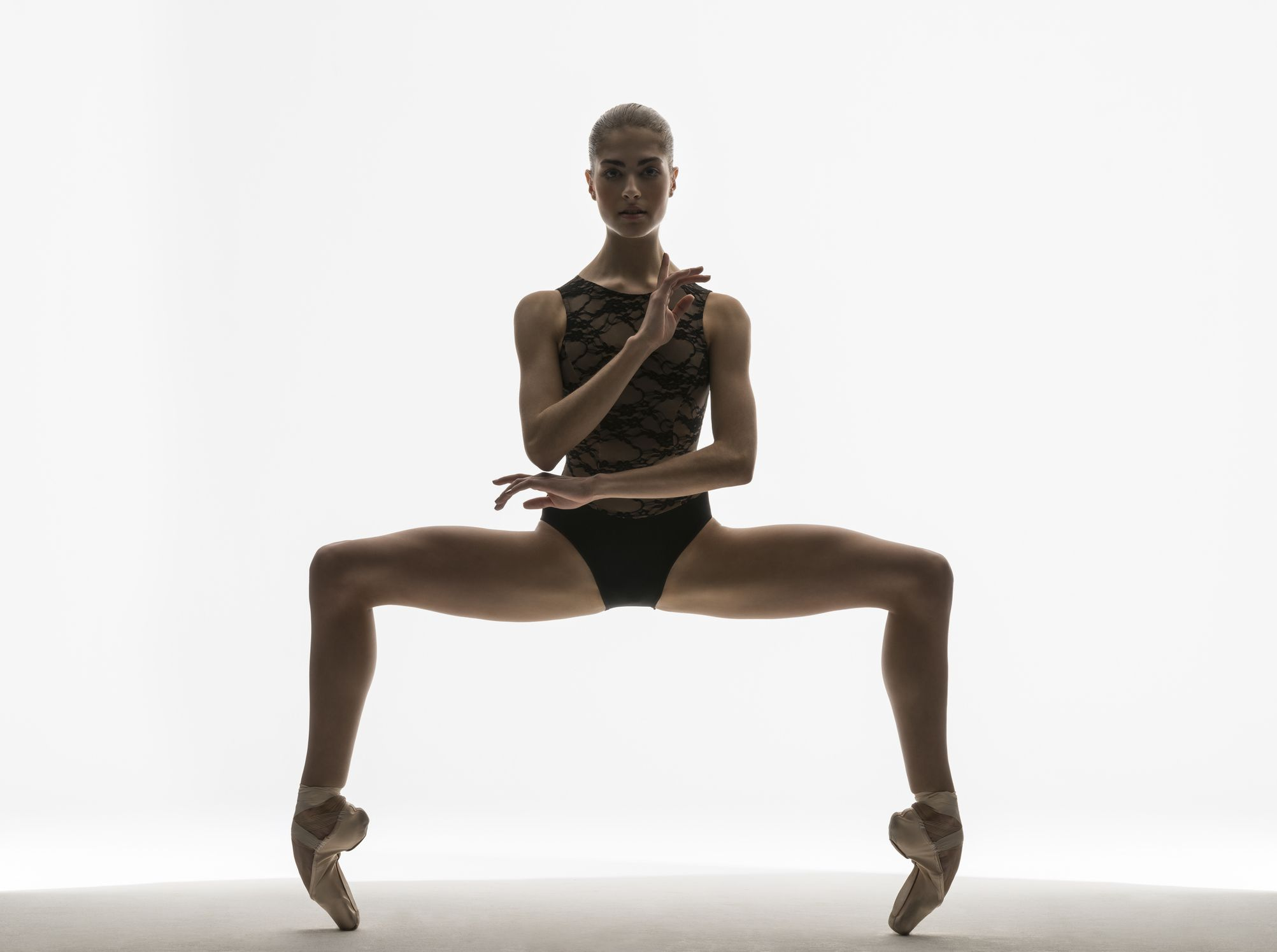 ballerina in grand plie on pointe looking at camera with her arms in front of her in studio