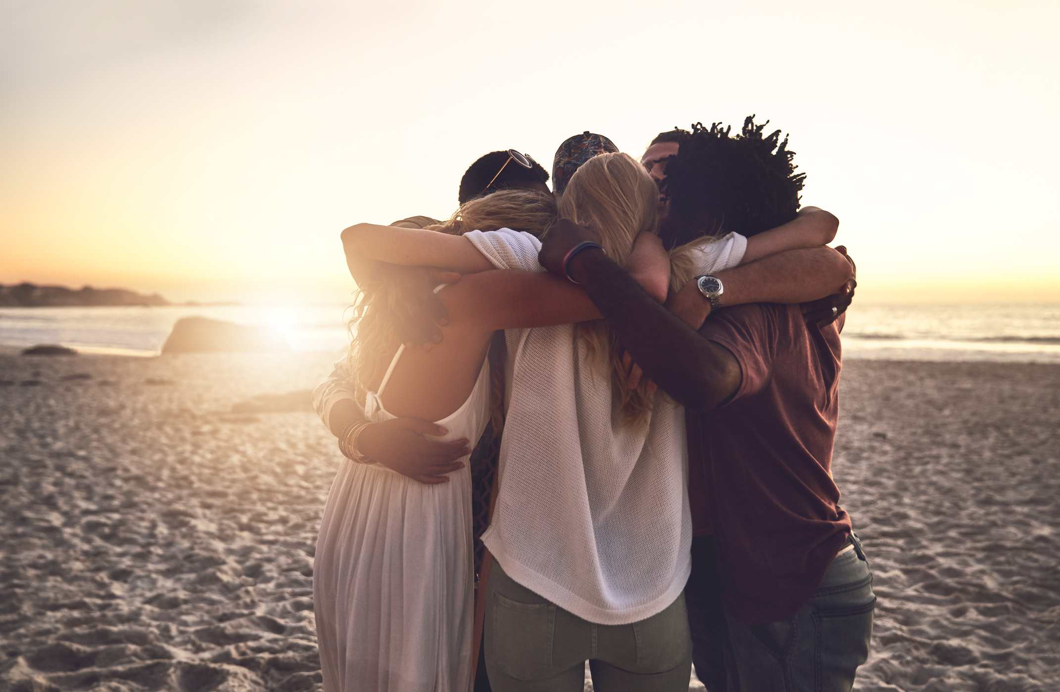 A group of friends hugging on the beach.