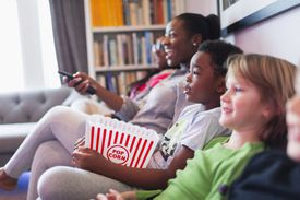 Family and friends watching movie and eating popcorn on living room sofa